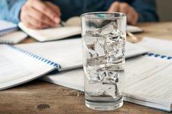 Exponeringsglas av vatten på ett träkontorsskrivbord Arkivfoto