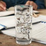 Exponeringsglas av vatten på ett träkontorsskrivbord Fotografering för Bildbyråer