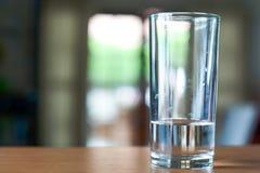 Exponeringsglas av vatten på ett träskrivbord Arkivfoton