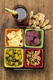 Exponeringsglas av vermut med ost, oliv, salami, muttrar och jordnötter Arkivfoto