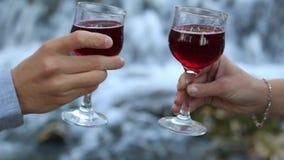 Exponeringsglas av vin i den manliga och kvinnliga handen i kontakt med de stock video