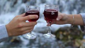 Exponeringsglas av vin i den manliga och kvinnliga handen i kontakt med de lager videofilmer