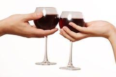 Exponeringsglas av vin i en kvinnlig och en manlig hand Arkivbild