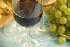 Exponeringsglas av vin, kort för tappning för druvacloseupmeny naturligt på en blå träbakgrund royaltyfri fotografi