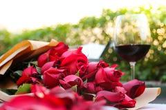Exponeringsglas av vin med röda rosor Arkivfoton