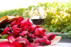 Exponeringsglas av vin med röda rosor Arkivbilder