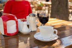 Exponeringsglas av vin och en kopp kaffe på ett utomhus- kafé med en bl Arkivbild