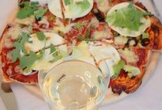 Exponeringsglas av vin och pizza Arkivbilder