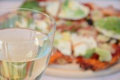 Exponeringsglas av vin och pizza Royaltyfri Bild