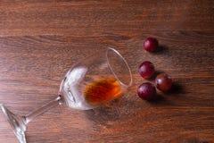 Exponeringsglas av vin och röda druvor på en träbakgrund arkivfoton