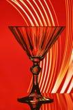 Exponeringsglas av vin på en röd bakgrund Royaltyfria Bilder