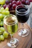 Exponeringsglas av vit och rött vin, nya druvor ombord Royaltyfria Foton