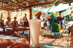 Exponeringsglas av vitt krämigt mjölkar drinkbananen Lassi på tabellen av kafét i Goa, Indien royaltyfri fotografi