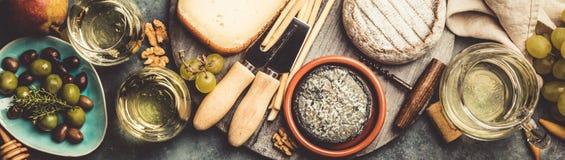 Exponeringsglas av vitt mousserande vin med ost, druvor, muttrar, oliv och honung arkivbild
