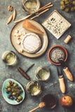 Exponeringsglas av vitt mousserande vin med ost, druvor som är tokiga, oliv royaltyfri foto