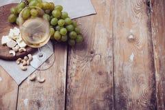 Exponeringsglas av vitt vin, druvor, kasjuer och mjuk ost Royaltyfria Bilder