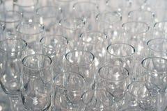 Exponeringsglas av vitt vin i rad på tabellen i pyramid Arkivfoton