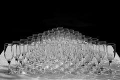 Exponeringsglas av vitt vin i rad på tabellen i pyramid Arkivfoto