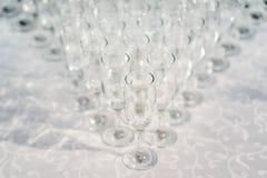 Exponeringsglas av vitt vin i rad på tabellen i pyramid Royaltyfri Bild