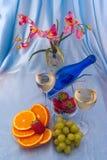 Exponeringsglas av vitt vin och blåttflaskan med apelsiner Royaltyfri Bild