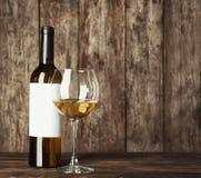 Exponeringsglas av vitt vin och flaskan med den tomma etiketten royaltyfri bild