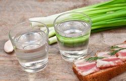 Exponeringsglas av vodka, lökar och bacon Royaltyfria Foton