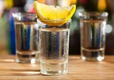 Exponeringsglas av vodka med citronen royaltyfria foton