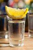Exponeringsglas av vodka med citronen Royaltyfri Foto