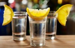 Exponeringsglas av vodka med citronen Arkivfoton