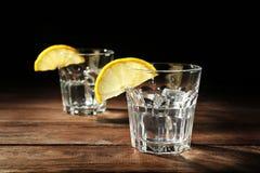 Exponeringsglas av vodka med citronen och is royaltyfria bilder