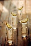 Exponeringsglas av vodka med citronen på trätabellen tona bild royaltyfri fotografi