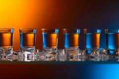 Exponeringsglas av vodka med is på en exponeringsglastabell royaltyfri fotografi