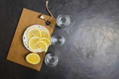 Exponeringsglas av vodka Och citron som skivar på en platta Ställe för din text Royaltyfria Bilder