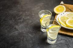Exponeringsglas av vodka Och citron som skivar på en platta Ställe för din text Royaltyfria Foton