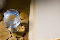 Exponeringsglas av vodka och en forntida bok Arkivbilder