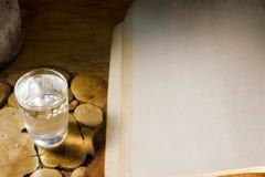 Exponeringsglas av vodka och en forntida bok Royaltyfri Foto