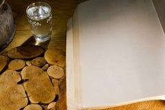 Exponeringsglas av vodka och en forntida bok Royaltyfria Foton