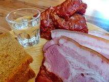 Exponeringsglas av vodka på bakgrunden av de hemlagade aptitretarna - rökt kött, bröd Naturlig mat, aptitretare closeup Fotografering för Bildbyråer