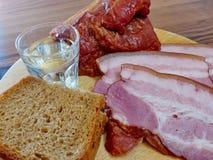 Exponeringsglas av vodka på bakgrunden av de hemlagade aptitretarna - rökt kött, bröd Naturlig mat, aptitretare closeup Royaltyfri Foto