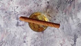 Exponeringsglas av whisky med den iskuber och cigarren stock video