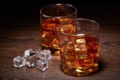 Exponeringsglas av whisky med isar royaltyfri foto