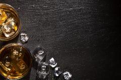 Exponeringsglas av whisky med is på den svarta stentabellen royaltyfri foto