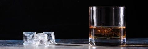 Exponeringsglas av whisky med is på tabellen Royaltyfri Foto