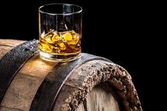 Exponeringsglas av whisky med is på gammal ektrumma Royaltyfri Bild