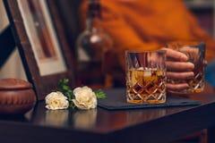 Exponeringsglas av whisky och blommor, stilleben, filmisk effekt royaltyfri bild