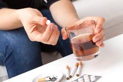 Exponeringsglas av whisky och cigaretten arkivfoton