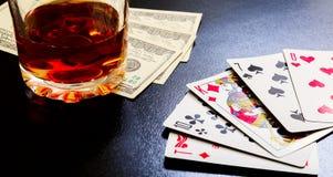 Exponeringsglas av whisky och spelakort och dollarräkningar på ett svart skrivbord på trätabellen Royaltyfri Foto