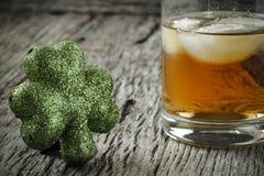 Exponeringsglas av whisky och växter av släktet Trifolium arkivbilder