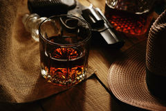 Exponeringsglas av whisky, revolvret och hatten Arkivbild