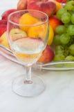 Exponeringsglas av wine och frukter Arkivbilder